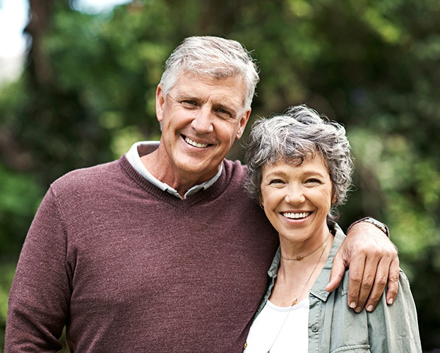 Man and woman smiling after all ceramic dental restorations
