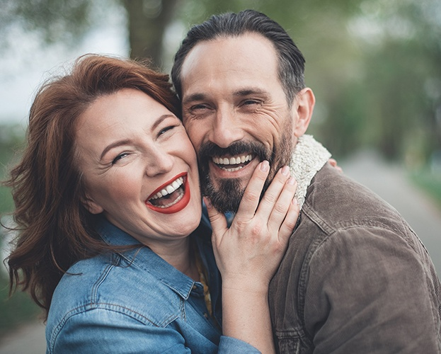 Man and woman smiling after dental implant tooth replacement