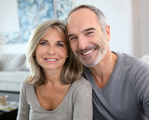 Older man and woman smiling after dental implant tooth replacement