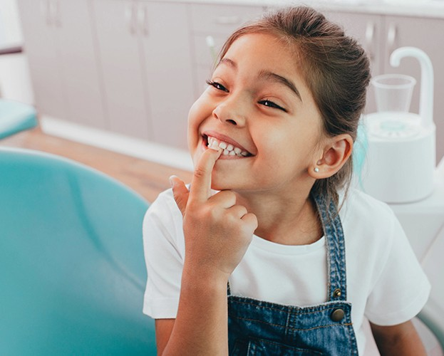 Little girl pointing to tooth colored filling