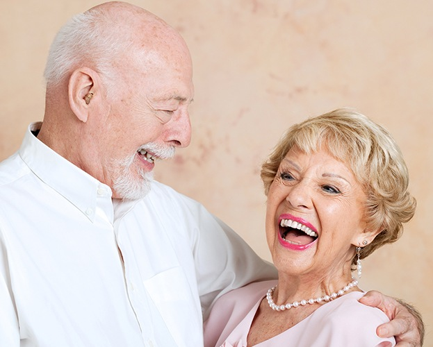 Older man and woman smiling after senior dentistry checkup