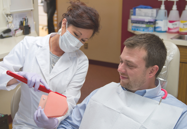 Dental team member showing patient how to brush teeth