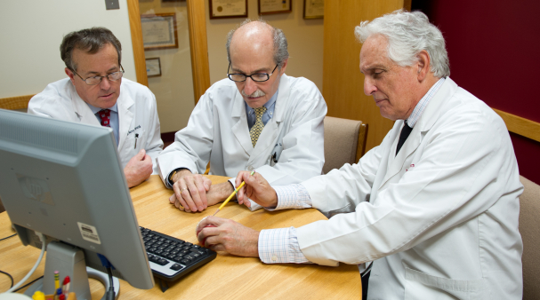 Three dentists collaborating on treatment plan
