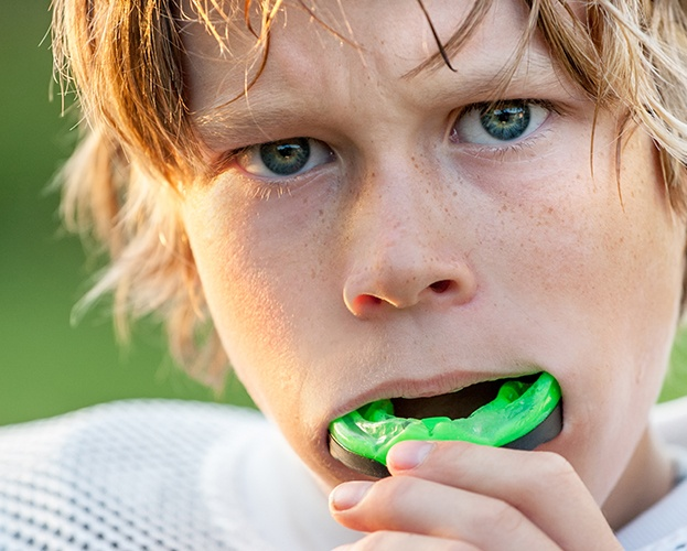 Teen placing athletic mouthguard