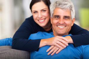 attractive older couple smiling on a sofa