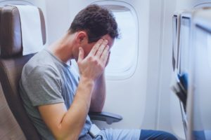 man in pain on plane
