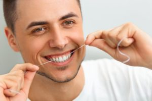 man smiling flossing keeping up with your oral hygiene through the quarantine